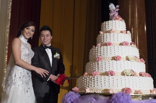 Happy couple: Newlyweds national squash player Delia Arnold and ex-national badminton doubles player Lin Woon Fui cutting the cake at their wedding reception in Sunway on Sunday.