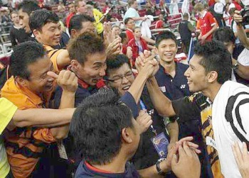 On a high: Mohd Hafiz Hashim being congratulated by Lee Chong Wei and team-mates after he beat Denmark's Joachim Persson to help Malaysia qualify for the semi-finals of the Thomas Cup.