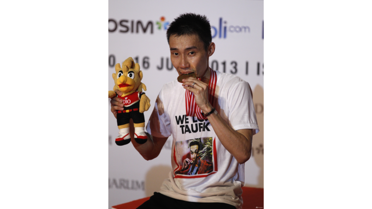 Malaysia's Lee Chong Wei bites his medal after defeating Marc Zwiebler of Germany during their final match at the Indonesia Open badminton championship at Istora stadium in Jakarta, Indonesia.