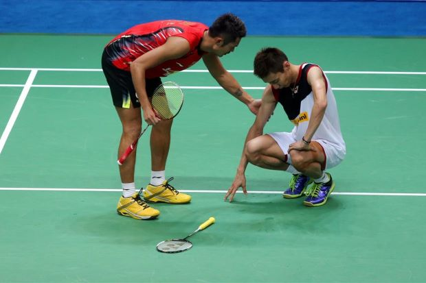 Lin Dan checks on Lee Chong Wei after the Malaysian world No.1 suffered leg cramps during their World Championships final. Lin Dan won after Chong Wei retired whilst trailing 17-20 in the third game.
