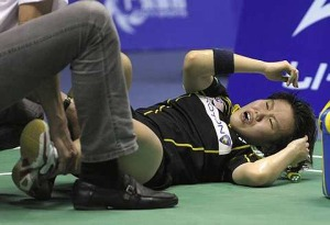 Painful end: Julia Wong grimacing while receiving treatment for a knee injury during Monday's match against Yip Pui Yin of Hong Kong.The shuttler returned home Tuesday (below) and was whisked to the hospital for medical tests on the extent of the injury.