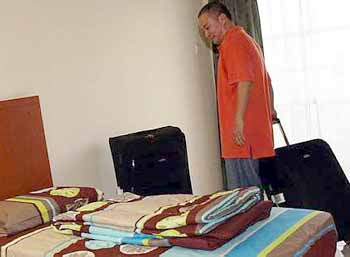 Room for improvement: Malaysia's new singles coach Hendrawan checking into his room at the hostel in Mount Kiara Monday.