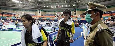 Masked protector: Malaysia's Sabrina Chong and Ong Jien Guo walking past a masked security personnel after losing to Chinese mixed doubles pair He Hanbin-Yu Yang yesterday.