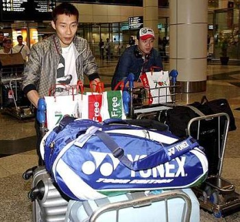 It's good to be home: Lee Chong Wei and Koo Kien Keat pushing their trolleys out of the arrival hall at the KLIA on their return from Paris yesterday.