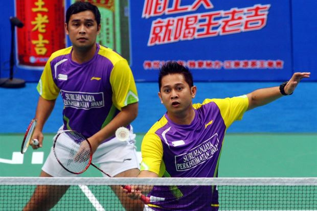 Sweet taste of victory: Malaysia's Mohd Fairuzizuan Mohd Tazari (left) and Mohd Zakry Abdul Latif in action against Russia's Vladimir Ivanov-Ivan Sozonov during their second round match of the World Championships at Tianhe Gymnasium in Guangzhou on Wednesday.