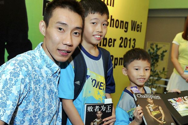 Lee Chong Wei takes a photo with young fans Lim Yu Hong, 10, and Lim Yu Ming, 7, at an autograph session at the Malaysia Sports & Health Fair 2013. He will be skipping the China Open to allow his ankle to heal but hopes to make it to the Hong Kong Open and the Super Series Finals.