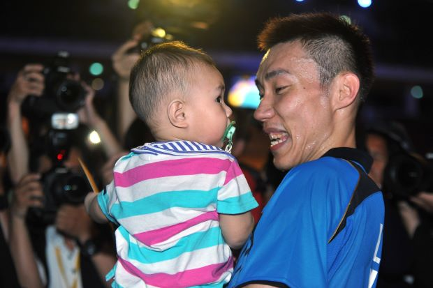 A beaming Lee Chong Wei carries his son, Kingston, after winning the Malaysian Open badminton championship title for the 10th time on Sunday at Putra Stadium in Bukit Jalil.
