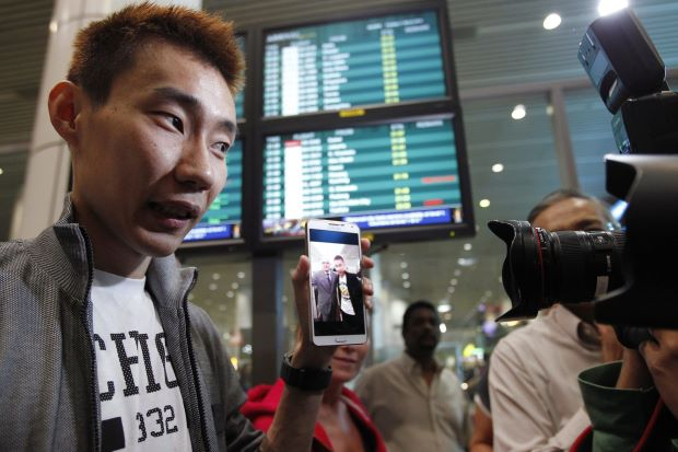 Lee Chong Wei, on arrival at the Kuala Lumpur International Airport, showing photographers a picture of him and Andrew Nari, the chief steward on MH370 which has disappeared. Chong Wei had met Nari on a previous flight.