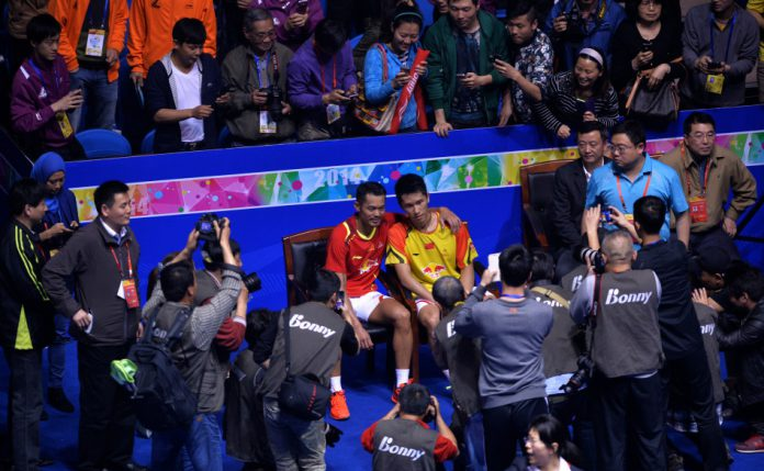 Lin Dan happily posed for pictures with Tian Houwei after the match