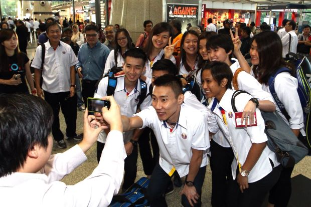 Lee Chong Wei and his teammates are posing for pictures before their departure for New Delhi