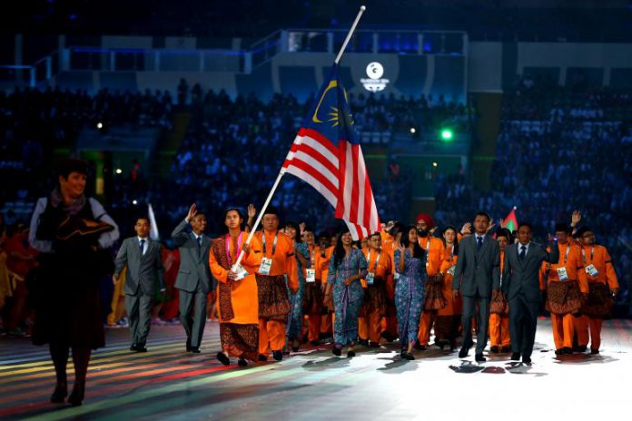 Flag bearer and Cyclist Fatehah Mustapa of Malaysia flies the flag at half mast during the Opening Ceremony for the Glasgow 2014 Commonwealth Games at Celtic Park on July 23, 2014 in Glasgow, Scotland. Quinn Rooney/Getty Images