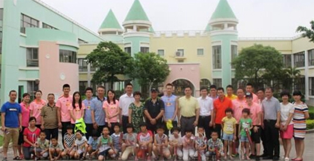 The Chinese badminton team take photos of themselves with the children.