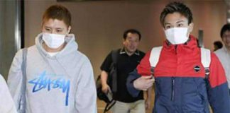 Kento Momota (r) and Kenichi Tago arrive at Narita airport Thursday morning.