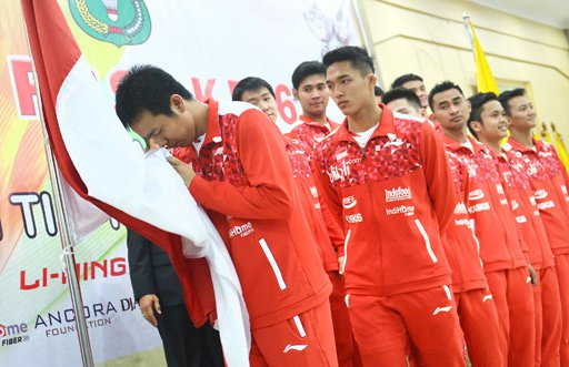 Indonesian Thomas Cup team captain Hendra Setiawan kisses Indonesia's national flag before departing to China for the 2016 Thomas & Uber Cup finals. ( Antara/Prasetyo Utomo)
