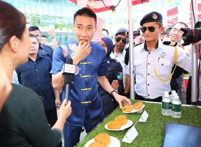 Lee Chong Wei tastes a piece of 'Moon Cake' during the mid-autumn festival. (photo: Sinchew)