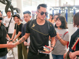 Lin Dan takes pictures with his fans.