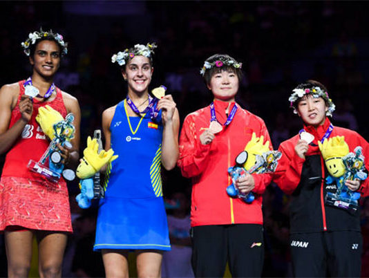 Carolina Marin of Spain (second left) defeats India's PV Sindhu (left) 21-19, 21-10 for her third world title. (photo: AFP)