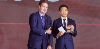 Kento Momota (R) receives the 2019 Male Player of the Year award from BWF President Poul-Erik Høyer. (photo: BWF)