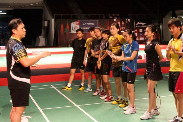 Words of wisdom: Tan Kim Her (left) speaking to the Malaysian squad. He is in charge of grooming the younger doubles players for the future.