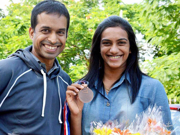 P Gopichand (L) with P.V. Sindhu after she returned home with a bronze medal at badminton World Championships in Copenhagen.