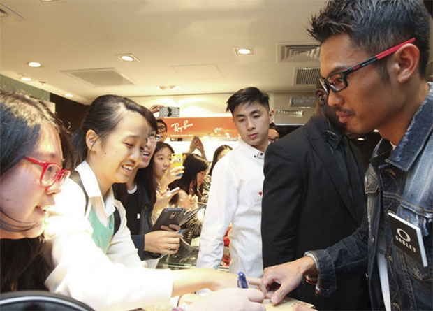 Wearing a slick pair of eyeglasses, Lin Dan signs autographs for his fans