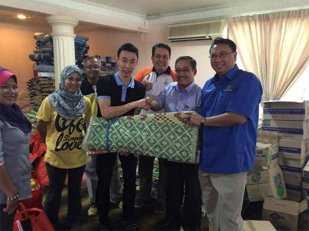 Lee Chong Wei hands over his donations to the flood relief officer (Photo: Lee Chong Wei's FB)