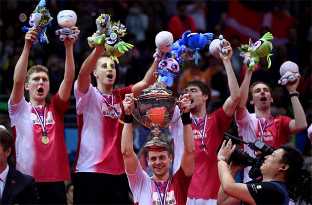 Hans-Kristian Vittinghus (C) of Denmark holds the Thomas Cup trophy between his teammates during the awards ceremony. (photo: AFP)