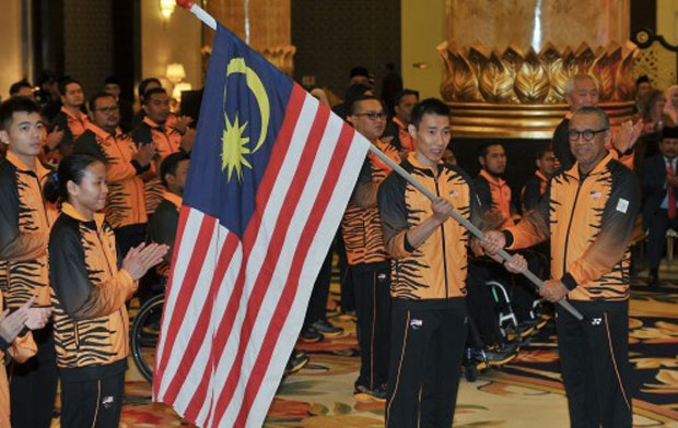Al Amin hands the Malaysian flag to Lee Chong Wei. (photo: AFP)