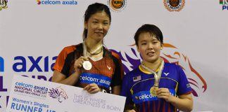 Goh Jin Wei and Soniia Cheah stand on the podium.