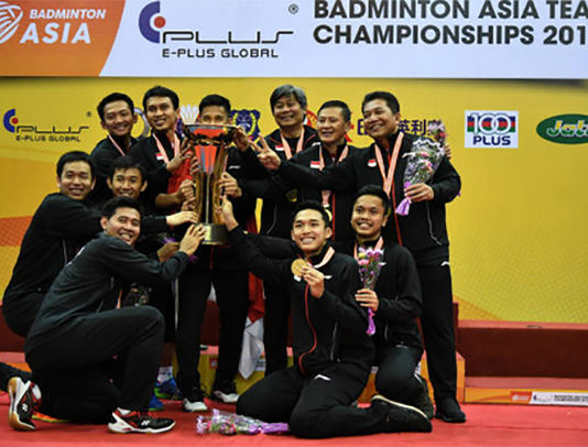 Indonesia team celebrates on the podium with the 2018 Badminton Asia Team Championships trophy. (photo: AP)