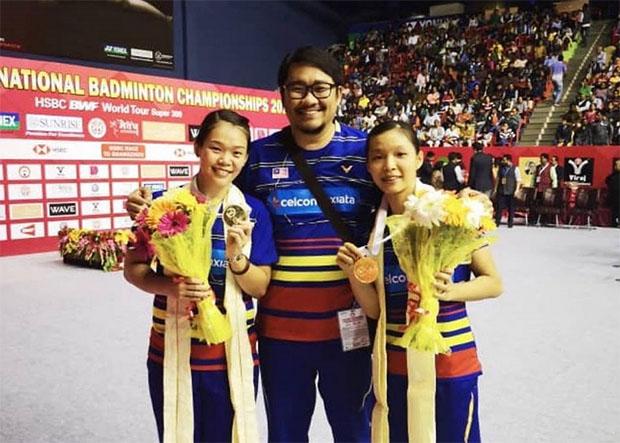 Chow Mei Kuan (R)/Lee Meng Yean (L) pose with their coach Rosman Razak after winning the 2018 Syed Modi International Badminton Championships. (photo: BAM's Facebook)