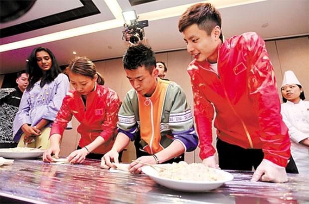 Huang Yaqiong, Zheng Siwei and Shi Yuqi make Chinese dumpling. (photo: AFP)
