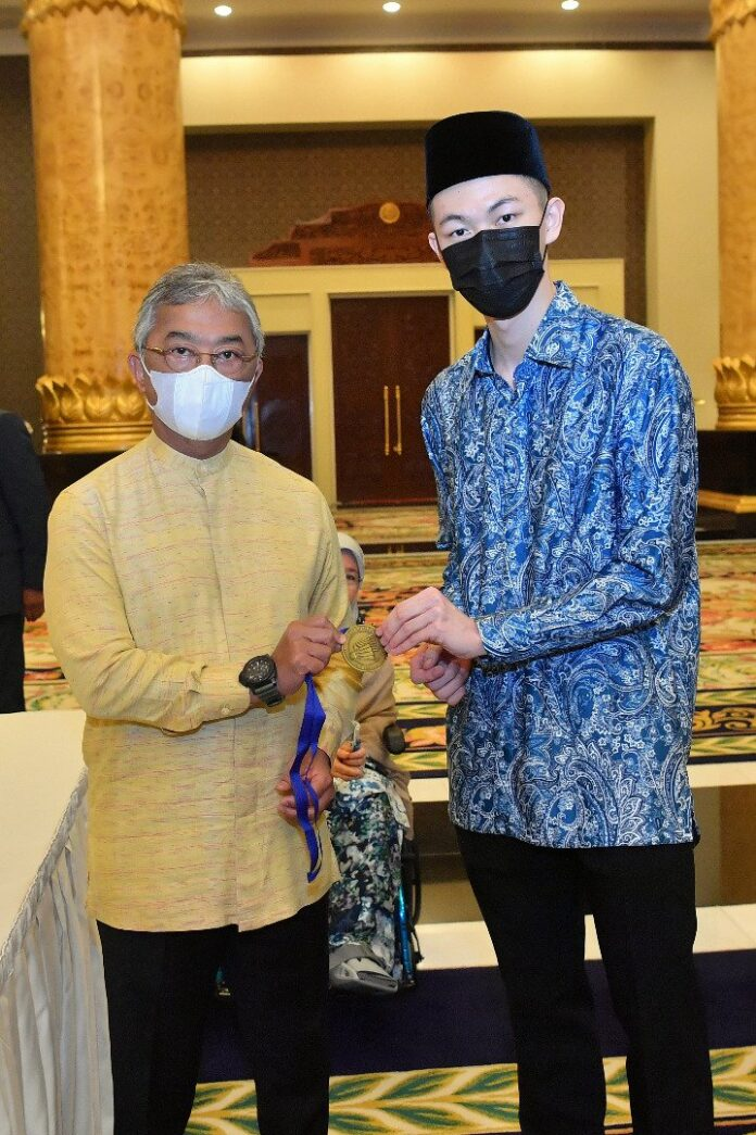 Lee Zii Jia shows the All England gold medal to the King of Malaysia. (photo: Bernama)