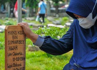 The wife of the late Markis Kido, Richasari Pawestri, prays after her husband's funeral at the Kebon Nanas TPU, East Jakarta. (photo: ANTARA FOTO/ Fakhri Hermansyah/aww)