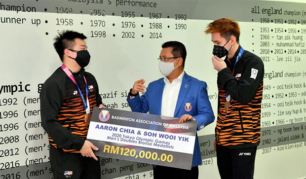 Aaron Chia/Soh Wooi Yik receive a check of RM120,000 from the President of BAM, Tan Sri Mohamad Norza Zakaria. (photo: Bernama)